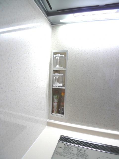 After:リフォーム施工中に奥様より「調味料を置くスペースがなく困っている」とのお話を伺い急遽、キッチンパネルを加工して「埋め込みスパイスラック」に仕上げました。