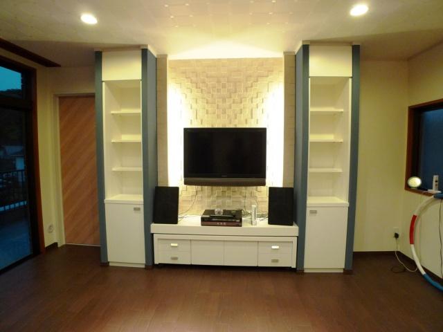 After:床材は寝室と同じエクオスロッゾです。 結露がお悩みだった奥様にTVボード正面にイナックスのエコカラットを(プレシャスモザイク ぺトラスクエア)提案。ライティングによる陰影が美しく壁面を照らしています。又、収納棚側面にもブルーでヌリカラットを塗りアクセントをつけてみました。