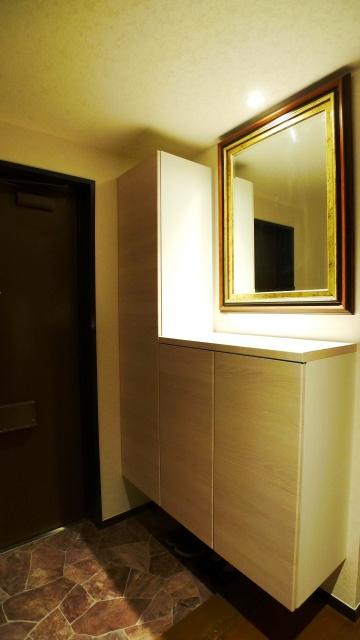 After:玄関収納も機能的で高級感のあるものにお取り替え。既存の鏡が映えるようにライトの位置も変更しました。