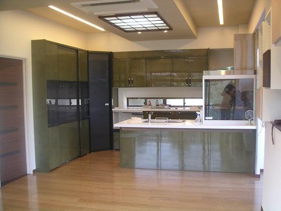 After:開放的なペニンシュラ型オープンキッチン。カラーはシックなグリーンメイプルをチョイス。