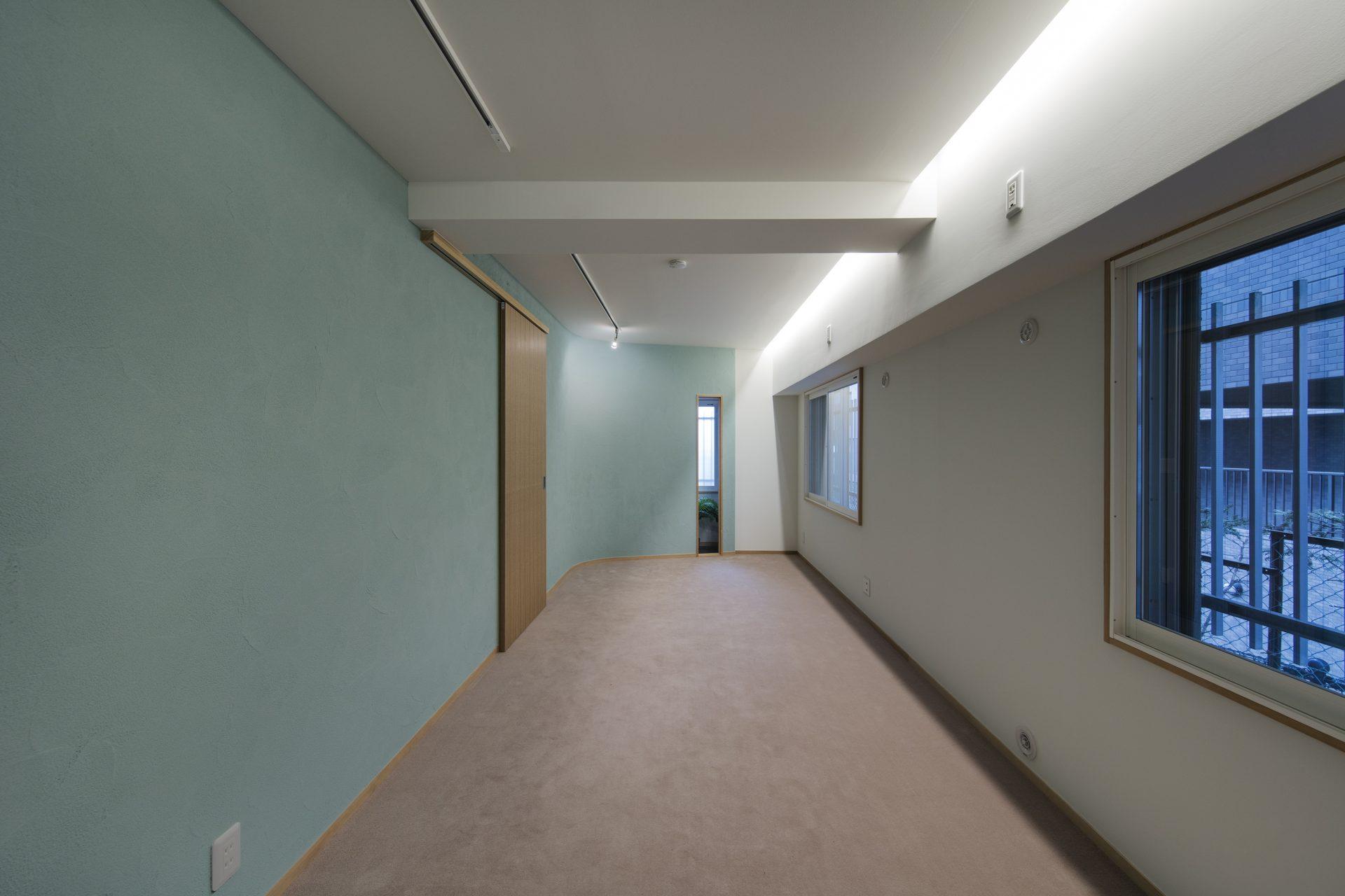寝室の壁は落ち着きある浅葱色の珪藻土。間接照明が 柔らかく照らします。